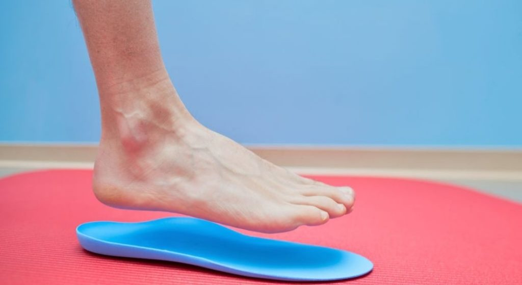 A man placing his foot on shoe insole