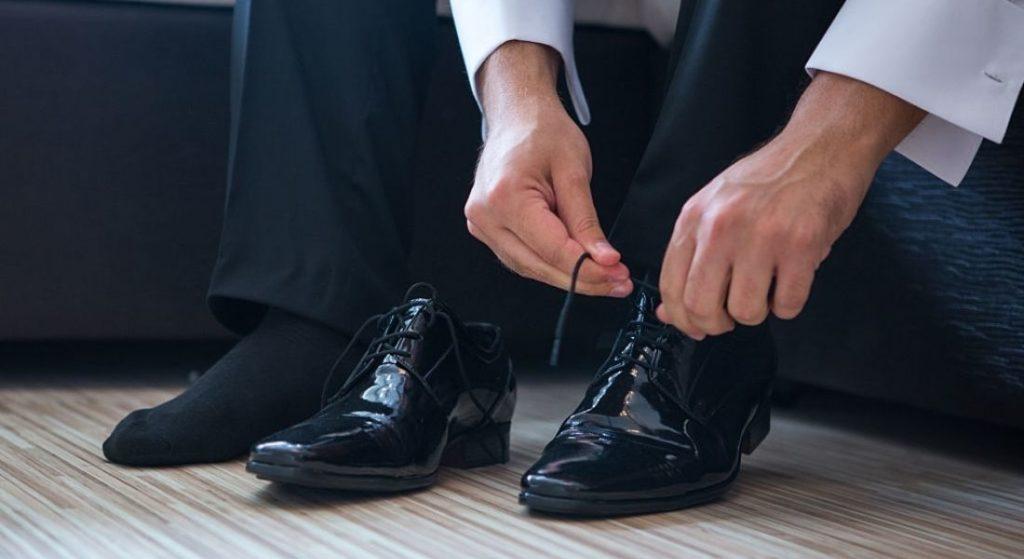 A man wearing the shoes to get ready for office